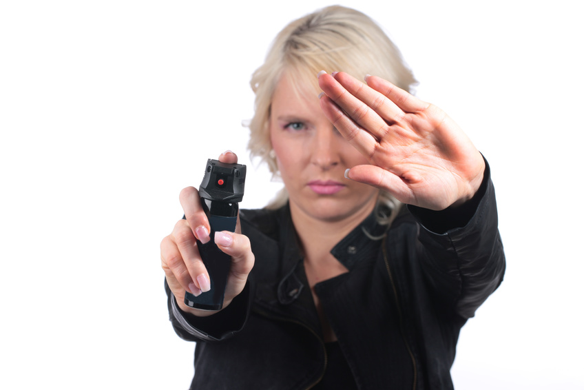 Self defense with pepper spray isolated