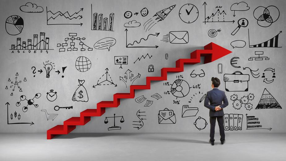 Business Mann bei Strategie Planung vor einer roten Treppe in Form von einem Pfeil